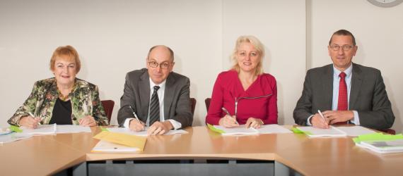 Mevrouw Schokker, de heer Dronkers, mevrouw Geldhof en de heer Offinga ondertekenen de samenwerkingsovereenkomsten
