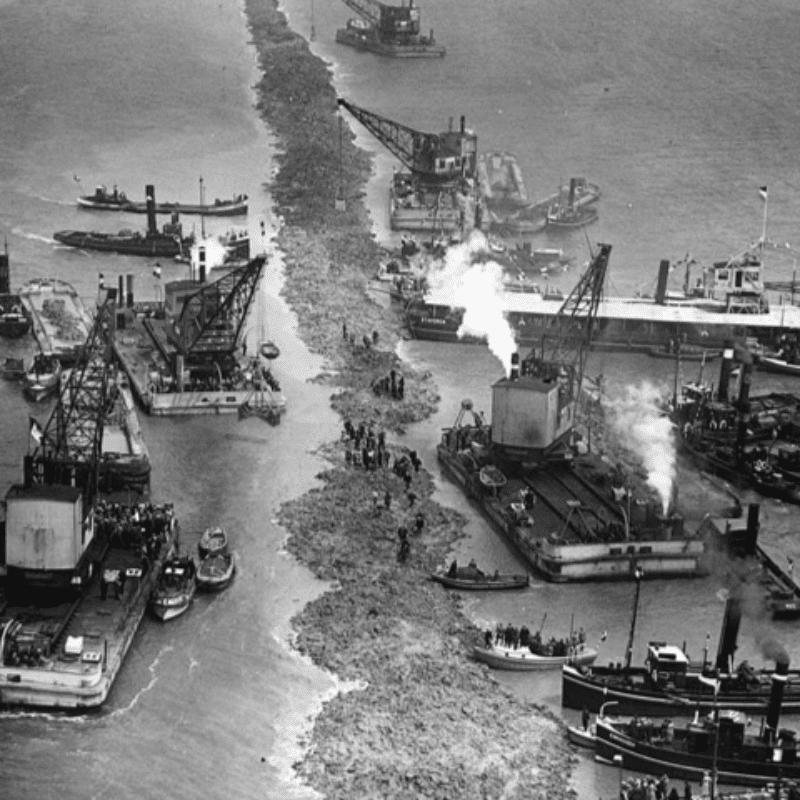 Het gaat om een oude foto van de Bouw van de Afsluitdijk in 1920. Hier is de bouw aan de Afsluitdijk net begonnen. Je ziet een zandbank aan de beide kanten varen boten.