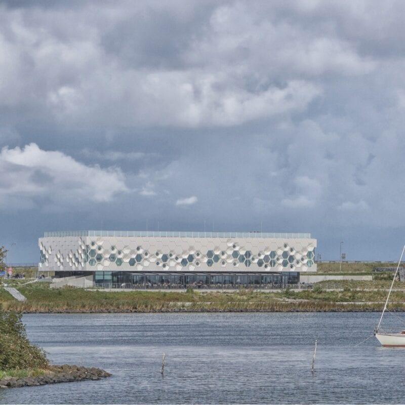 Foto van het Afsluitdijk Wadden Center aan de achterkant. Daarvoor zie je water. In dit water ligt een zeilboot.