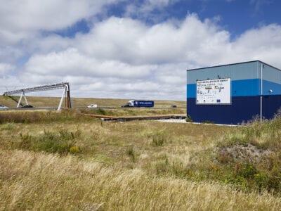Gebouw Blue Energy. Op de foto zie je een graslandschap. Aan de rechterkant staat een blauw gebouw met een wit spandoek. Verder aan de achterkant zie je een weg met een grijze paal boven de weg. Op de weg rijden auto's en vanaf het blauwe gebouw loopt een pijpleiding.