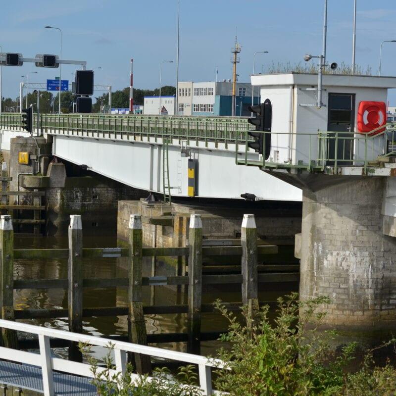 Bruggen op de Afsluitdijk. Wij kijken uit over een sluisbrug. Deze is wit en heeft een groene railing. Er staat ook een sluisgebouw aan de weg.