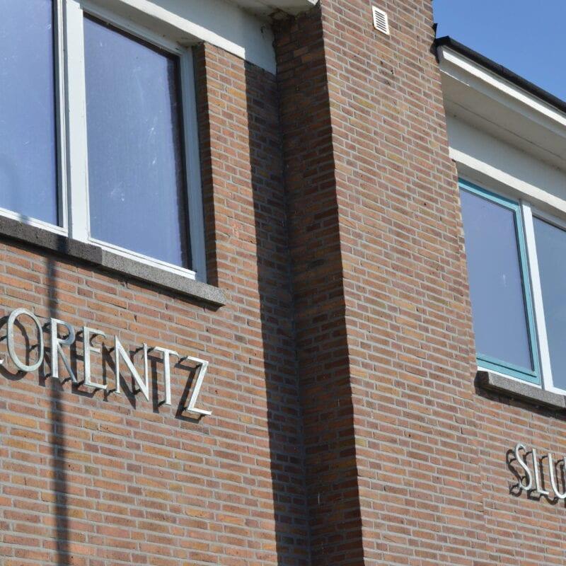 Lorentzsluisen. Wij kijken tegen de gevel van een sluis. Op het gebouw staat de naam van het gebouw.
