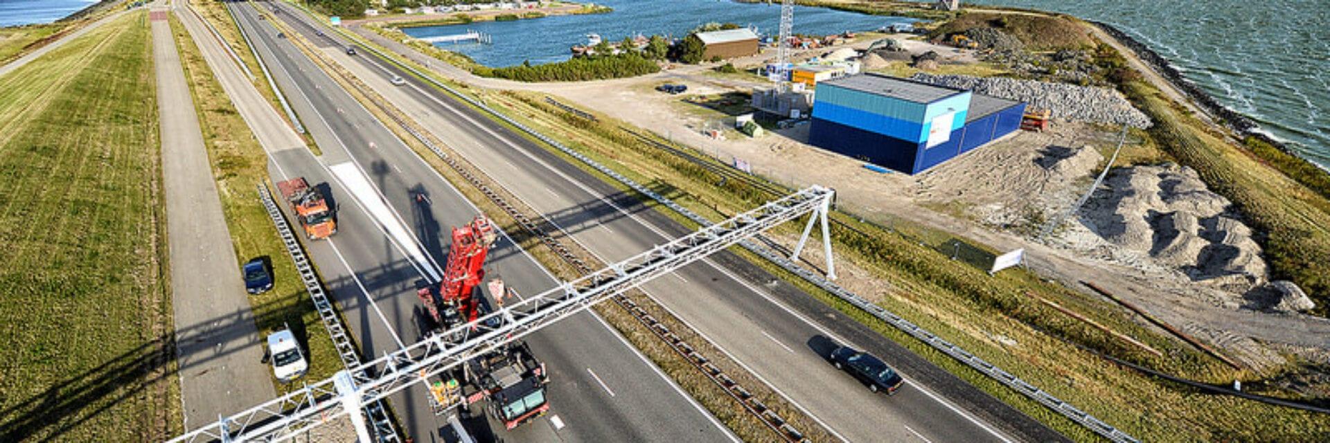 Blue Energy gebouw. We zien de twee wegen van de Afsluitdijk. Over de wegen loopt een metalen balk van linksonder naar rechts. Rechts zien we het blauwe gebouw van Blue Energy.