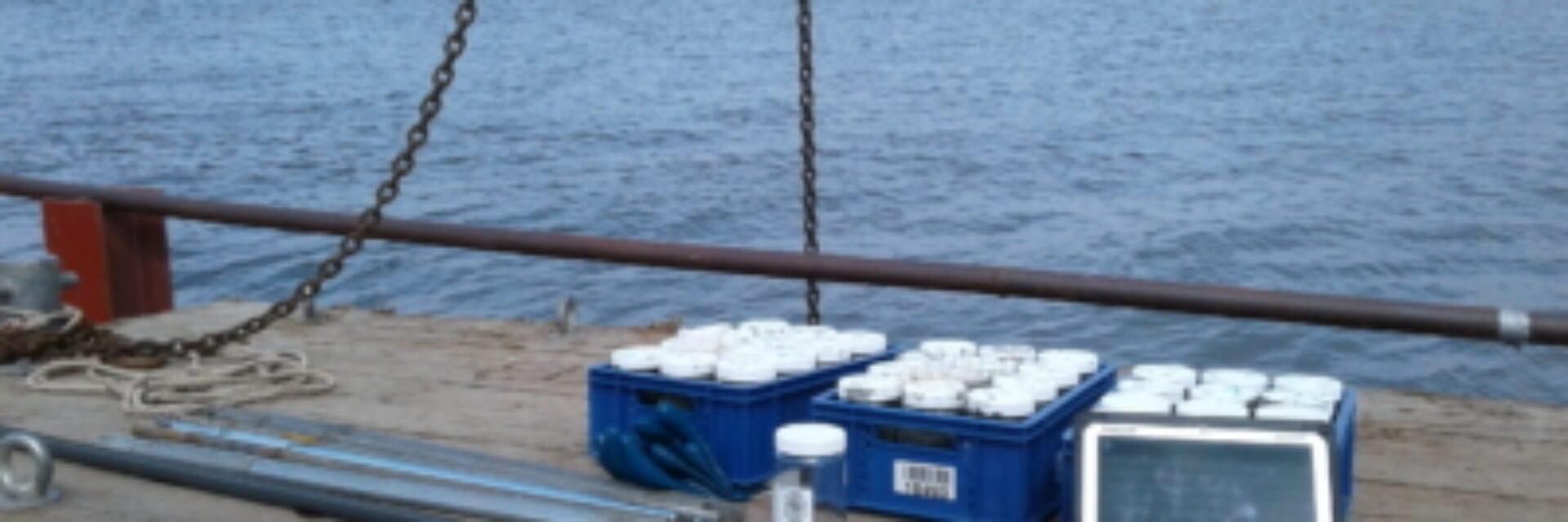 Bodemonderzoek bij de Vismigratierivier. Wij kijken uit op het water bij de Afsluitdijk. Daarvoor zien we de wal een grote kraan hijst iets in het water. Op de kant ligt onderzoeksmateriaal.