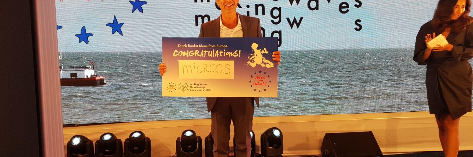 Micreos krijgt een prijs voor de beste innovatie van Nederland. Een man staat op het podium en houdt een cheque omhoog.