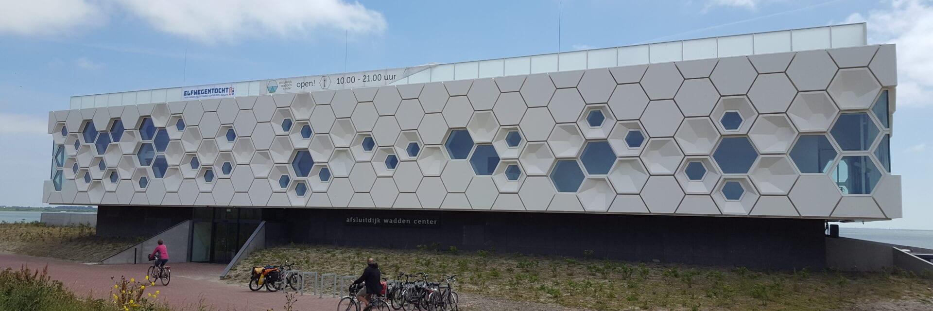 Het Afsluitdijk Wadden Center. We zien de voorkant van het museum. Dit is een wit gebouw met zeshoekige stenen en ramen. Voor zie je een fietspad met twee fietsers.