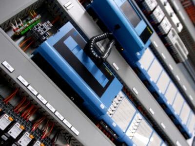 Systeemkast bij het Off Grid Test Centre. De binnenkant is blauw met witte knoppen. Je ziet ook rode kabels.
