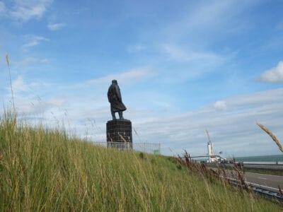 Op de foto staat het gras, standbeeld en rechts de weg. In het midden staat een sokkel met een grijs standbeeld van Lely. Bovenaan zie je de lucht.