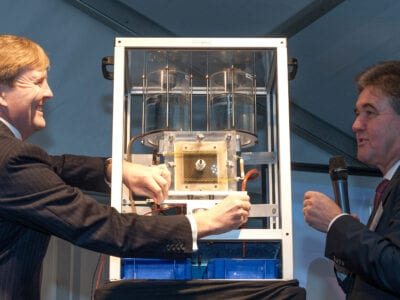 Koning Willem Alexander bezoekt Blue Energy. Hij staat aan een kleine versie van de Blue Energy technologie. Er staat nog een man omheen.