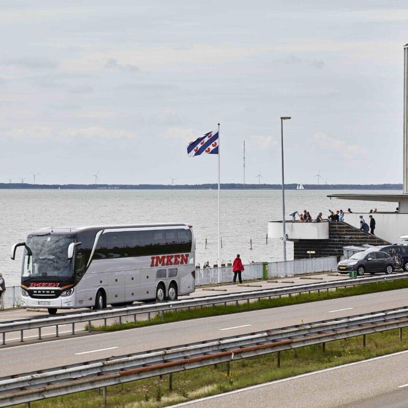 We zien de weg bij de Afsluitdijk. Aan de rechterkant staat de grote uitkijktoren, het Vlietermonument. We zien ook een geparkeerde bus met toeristen en een Friese vlag.