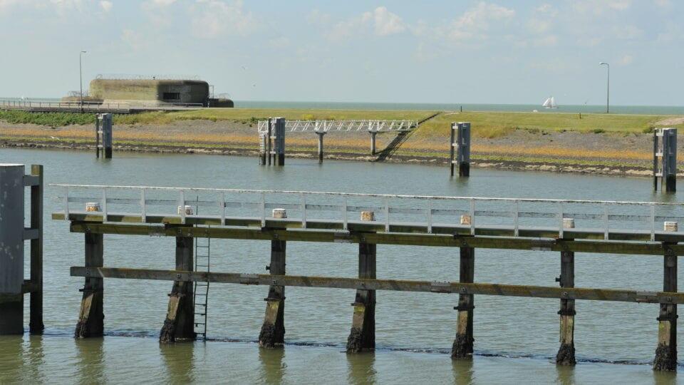 We kijken over het water van de sluis bij de Kazematten. Op de achtergrond zie je een bunker. Over het water staat er een aanmeerpaal.