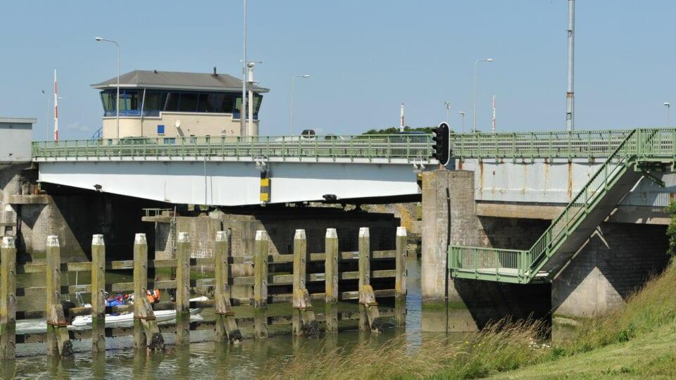 Op de foto zie je een brug boven de sluis van de Afsluitdijk. Links zie je een betonnen sluisgebouw.