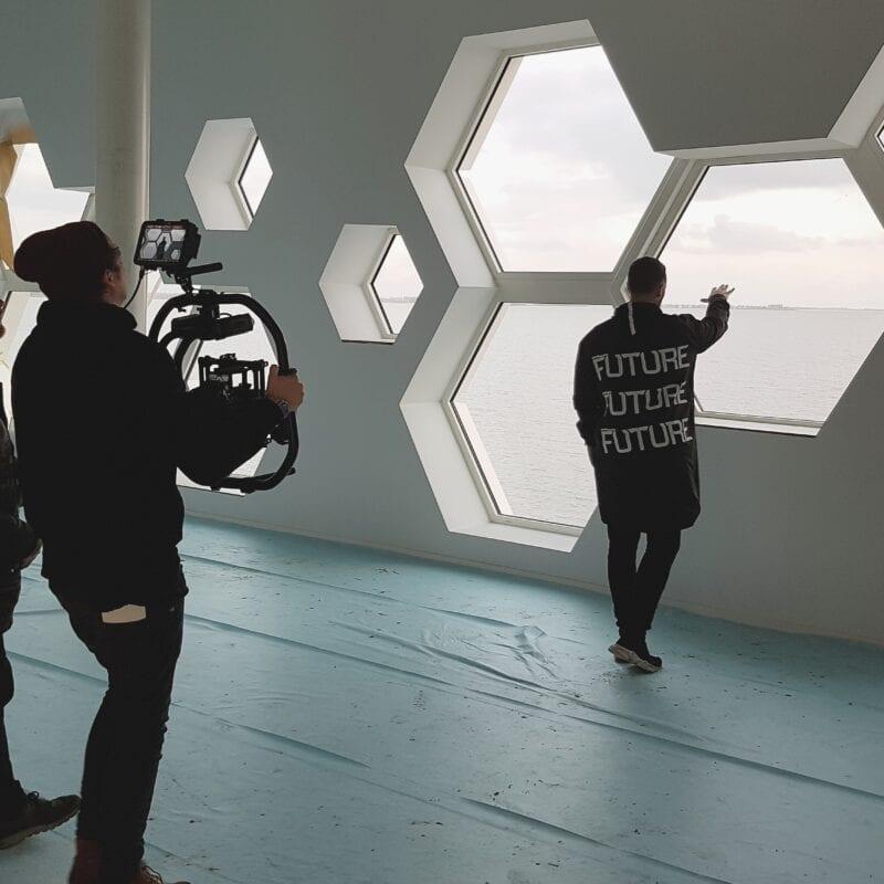 DJ Don Diablo komt langs bij het Afsluitdijk Wadden Center. Hij staat met zijn rug naar ons toe en er staat een cameraploeg. Hij kijkt uit het zeshoekige raam.
