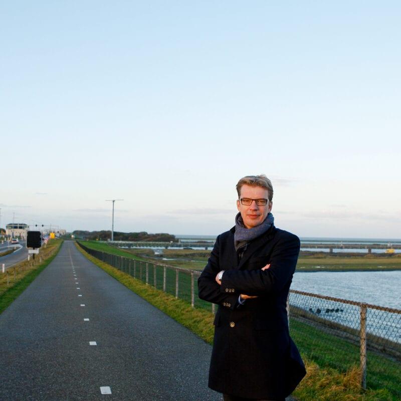 Douwe Faber vertelt over de energiedijk. Wij staat met zijn armen over elkaar voor het water van de Waddenzee.