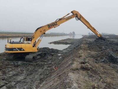 Graafwerkzaamheden, de eerste hap uit de kade van de Vismigratierivier. Een gele hijskraan is aan het graven.