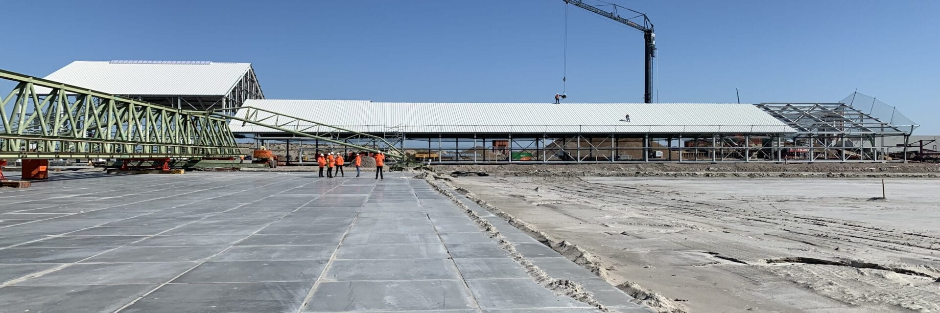 Bouw van de Levvel fabriek in Harlingen (maart 2019). Wij kijken uit over een werkterrein. Op de achtergrond zien we een grote loods met werkmensen en een hijskraan.