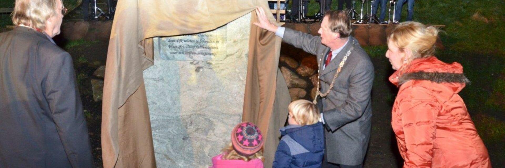 Herdenkingsbijeenkomst van de stormvloed 1916. De burgemeester onthult met twee kinderen en ouders het monument.