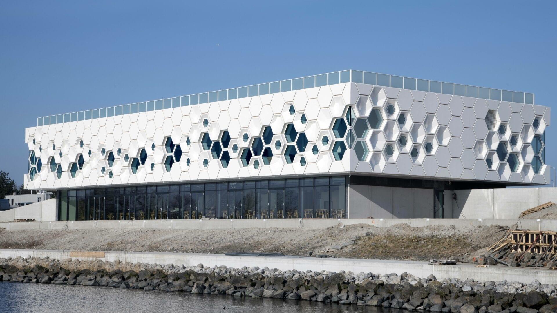 Afsluitdijk Wadden Center. Het witte gebouw van het museum. Dit bestaat uit zeshoekige stenen en ramen. Op de achtergrond zie je de weg bij de Afsluitdijk lopen.