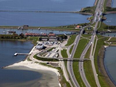 Luchtfoto van het Afsluitdijk Wadden Center. Wij kijken van boven op het museum. Daarnaast rechts zie je de wegen die op de Afsluitdijk zijn. Er loopt ook nog een horizontale weg over de weg. Dit is een brug. Linksboven zie je ook nog een aantal huizen van Kornwerderzand.