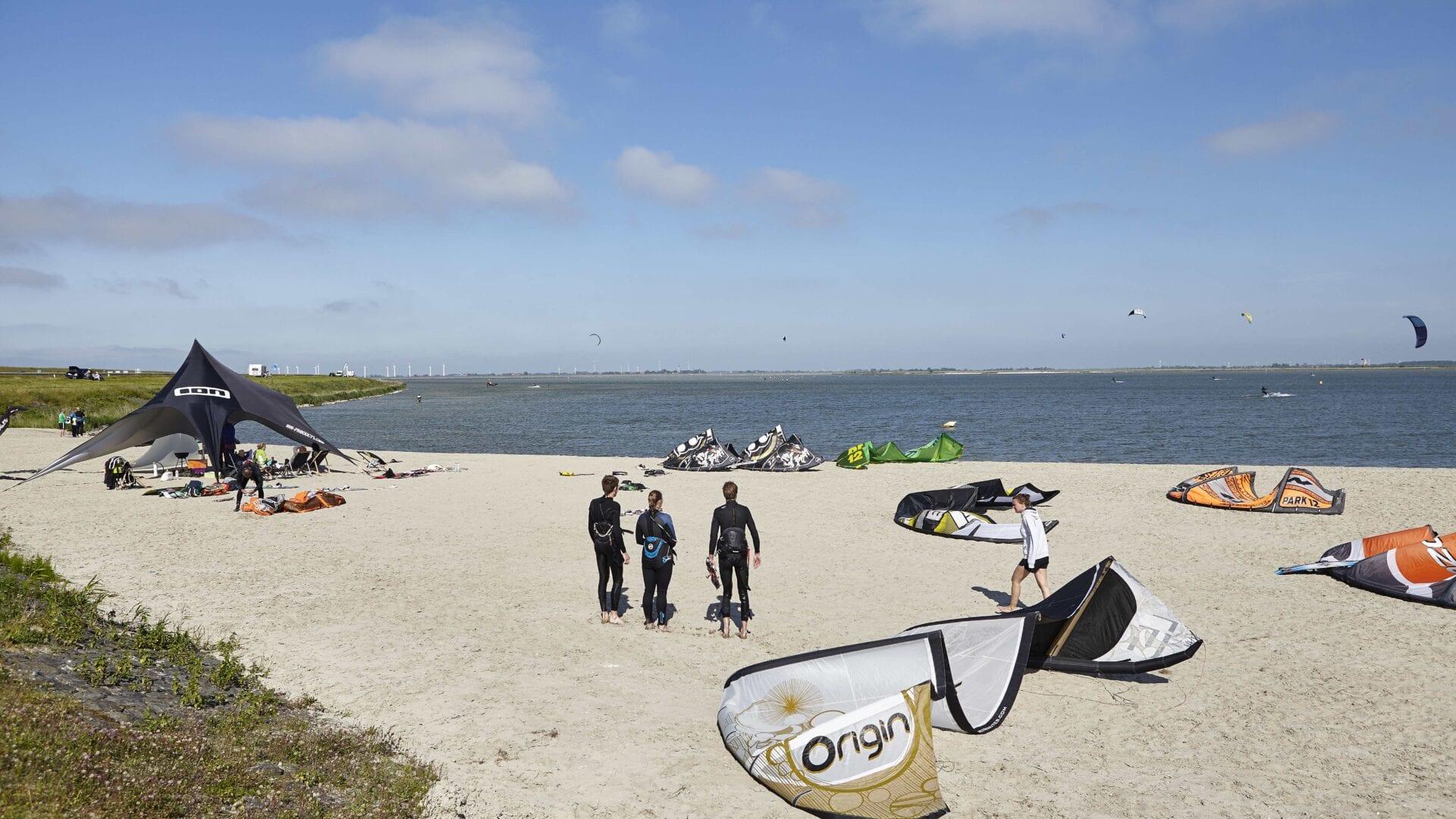 Kitesurfstrand bij de Afsluitdijk. Wij zien zand en water met verschillende kitesurfers.