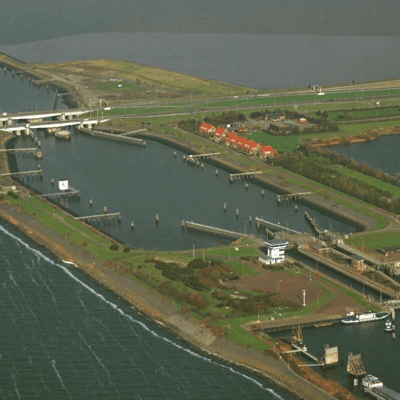 Luchtfoto van Kornwerderzand en de sluizen. We zien de Afsluitdijk van links naar rechts door beeld lopen. Deze is omringt door water. In het midden zie je twee verticale landstroken, dit is de sluis. Aan de zijkant van de sluis staan huizen. Dit is een oude foto want alle nieuwe gebouwen staan er nog niet.