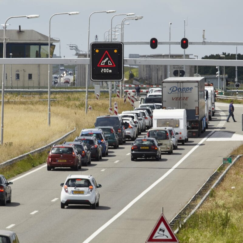 Verkeer op de Afsluitdijk door een open brug. Er staat een lange rij auto's en vrachtwagens bij de sluizen.