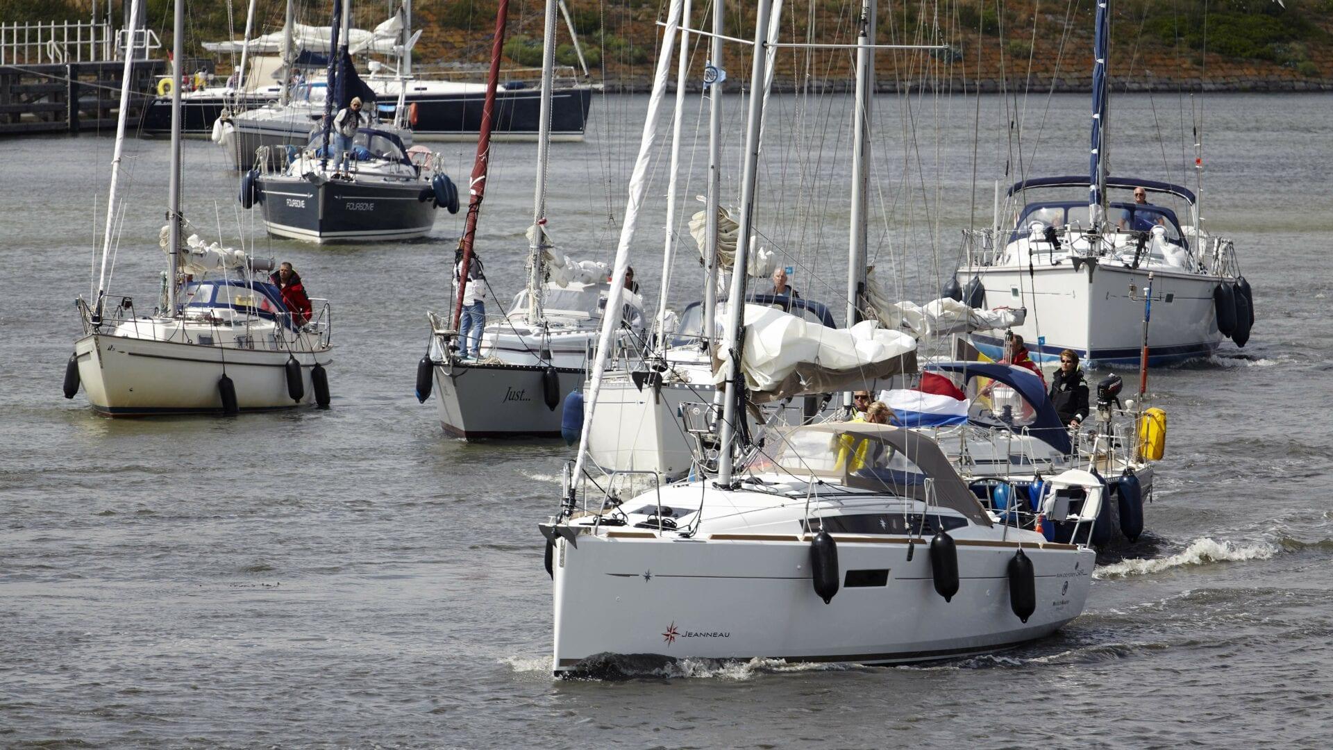 Bootjes die bij Kornwerderzand varen. Het zijn witte zeilboten die in het water liggen.