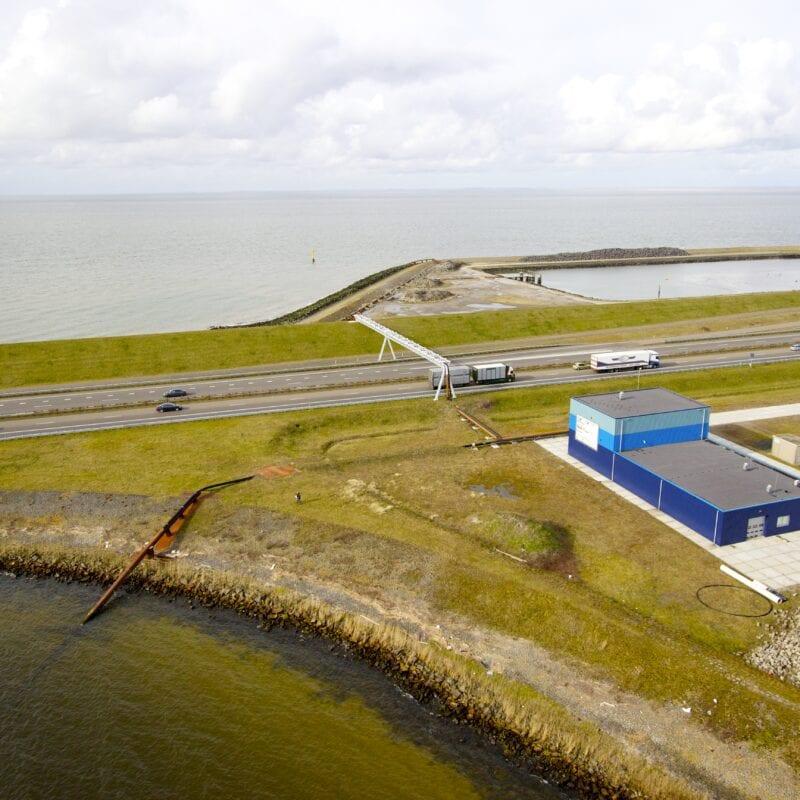 Gebouw van Blue Energy. Wij kijken van boven op de weg en het gras van de Afsluitdijk. Rechts zien we een blauw gebouw van Blue Energy.