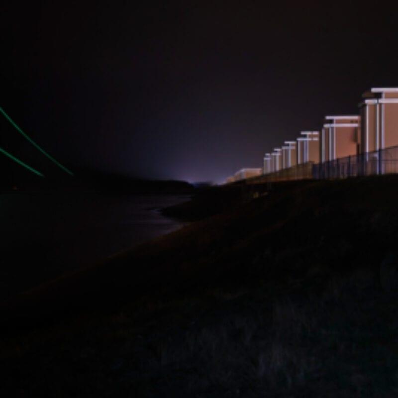 Gates of Lights in het donker met lichtstrips. Door reflectie van de koplampen lichten de strips links en rechts op.