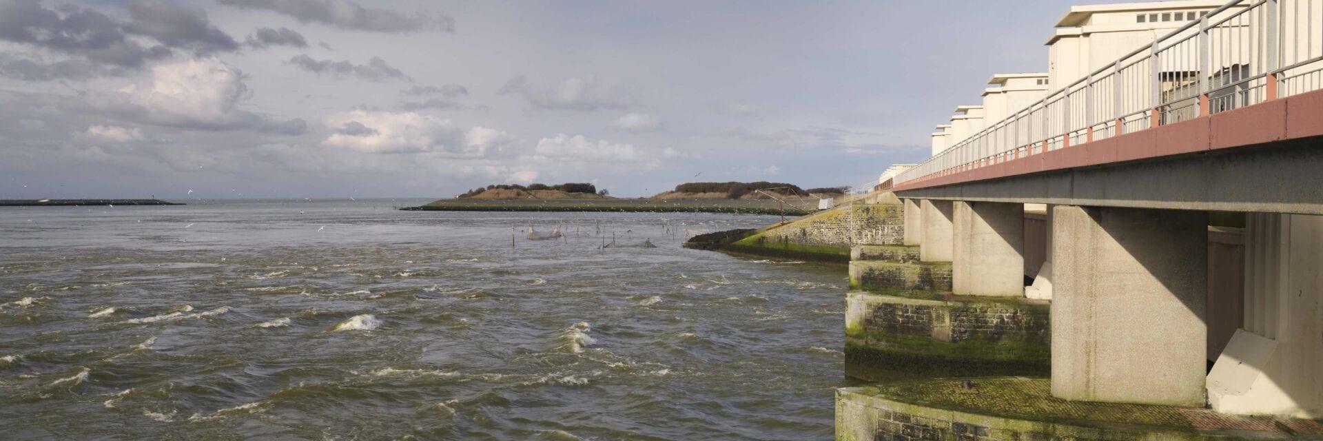 Afsluitdijk bij Den Oever, Stevinsluizen. We kijken uit over het water. Aan de rechterkant zien wij een hoge balustrade met de witte sluisgebouwen. Deze omlijsten de weg van de Afsluitdijk.