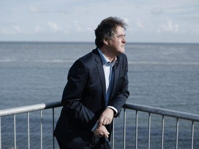 Het verhaal van Rik Siebers. Rik Siebers staat leunend bij een railing. Hij kijkt uit over het water.