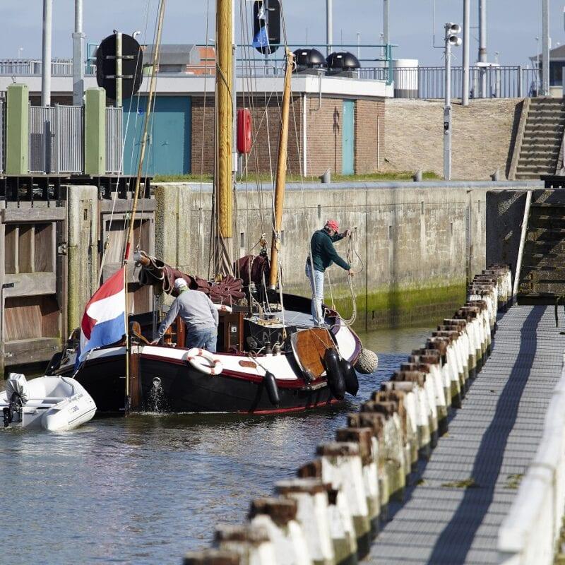 Er ligt een boot in de sluis bij Kornwerderzand. Dit schip vaart in laagwater en wacht tot de brug opengaat.