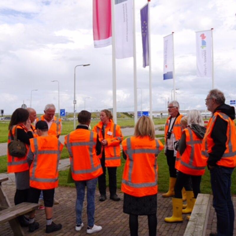Rondleidingen vanuit het infocentrum bij de Afsluitdijk naar het sluizencomplex. Een groep in oranje hesjes is verzameld bij de Afsluitdijk. Op de achtergrond zie je de weg van de Afsluitdijk.