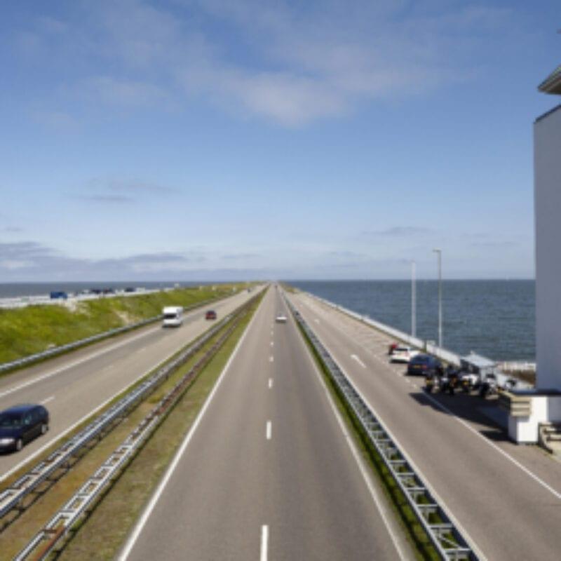 Vlietermonument langs de Afsluitdijk. Je ziet de weg lopen. Rechts zie je het lange, witte gebouw van het Vlietermonument.