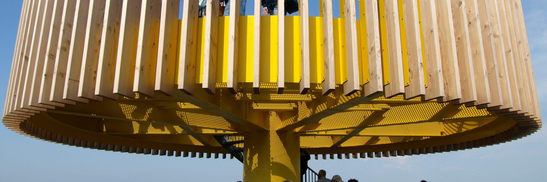Wij kijken uit over het water van de Waddenzee. In het midden van de foto zien we het belevingspunt bij Den Oever. Dit is een gele toren met twee schijven op elkaar. We staan ten hoogte van de eerste schijf en kijken tegen de bovenste schijf aan. Er staan veel mensen op de toren.