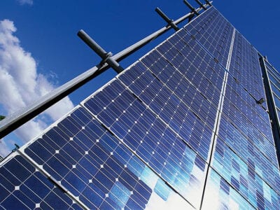Zonnepanelen om energie op te wekken. Daar achter zie je blauwe lucht met wolken.