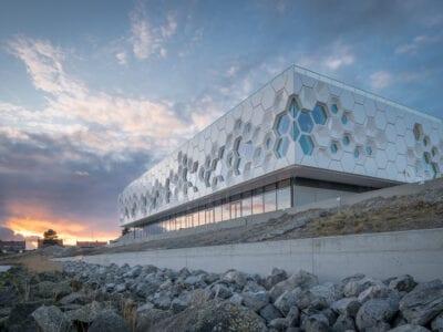 Afsluitdijk Wadden Center. Het witte gebouw van het museum. Dit bestaat uit zeshoekige stenen en ramen. Op de achtergrond zie je de zonsondergang boven Kornwerderzand.