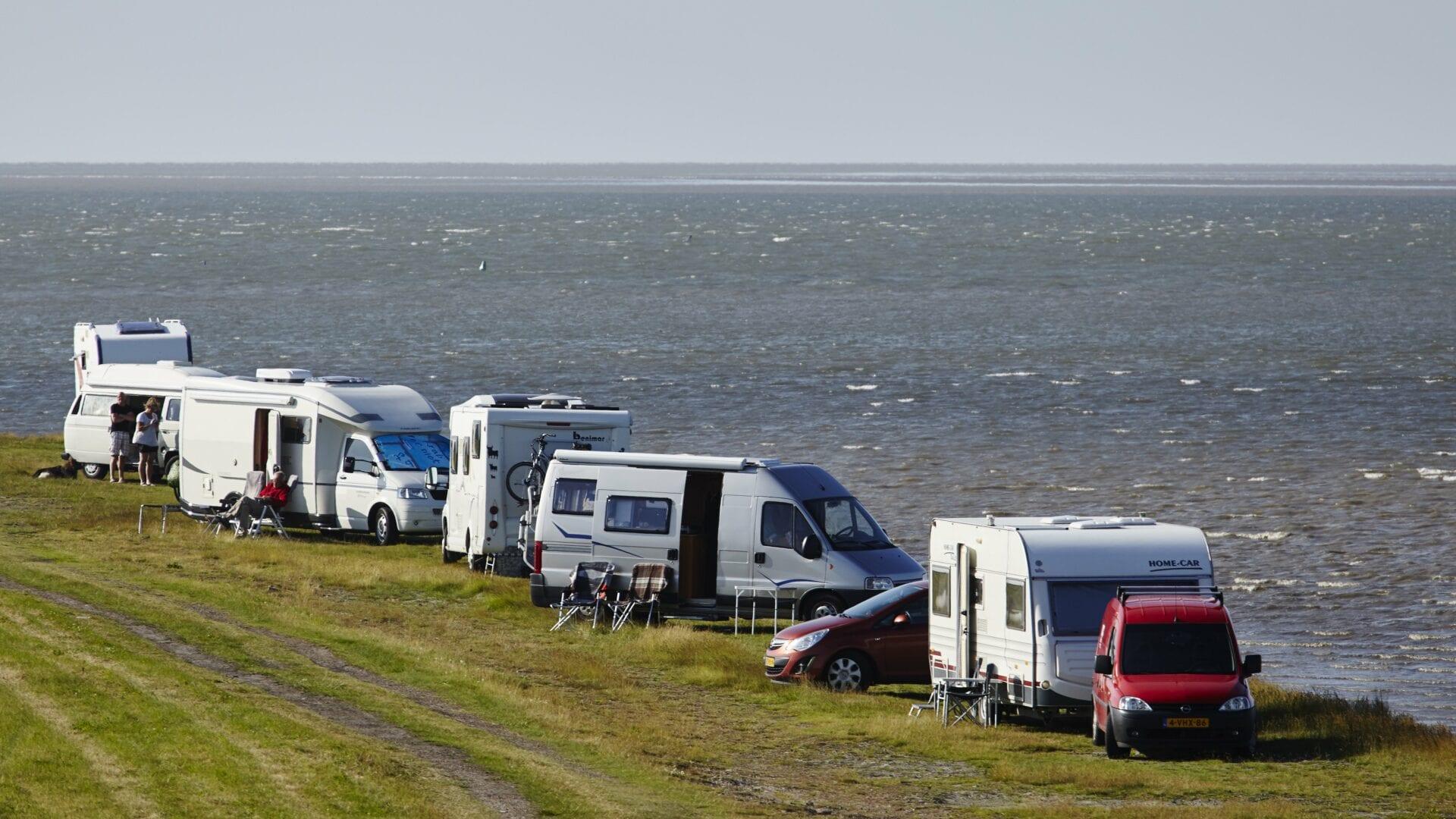 Kornwerderzand met campercamping. Aan het water zie je een stuk gras met vijf campers.