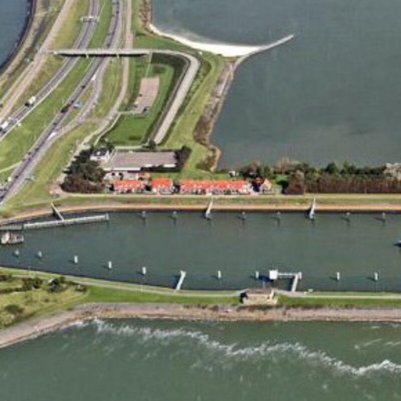 Luchtfoto van de sluizen bij Kornwerderzand. Van boven naar onder loopt de weg van de Afsluitdijk. In het midden zie je twee landstroken van links naar rechts lopen. Dit is de sluis bij Kornwerderzand. Je ziet in de ook een paar rode daken van Kornwerderzand en het kantoor van DNA.