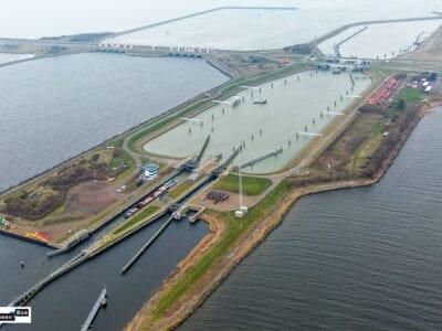 De verruimde sluis bij Kornwerderzand. We zien van links naar rechts de Afsluitdijk en de weg. Van boven tot onder lopen er twee landtongen. Dit is de sluis. Hier kunnen boten aanleggen. Ook zien we rechts een aantal daken van Kornwerderzand.