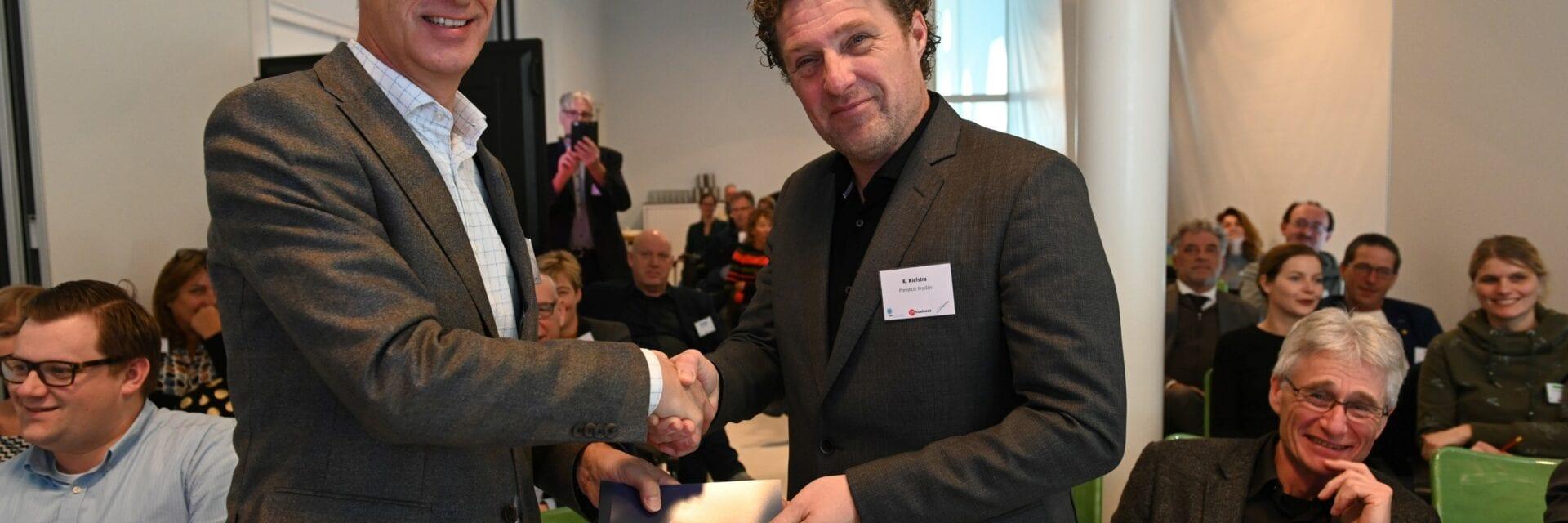 Symposium en handen schutten omdat de Afsluitdijk 700.000 bezoekers heeft getrokken in 2018. We zien een kamer vol mensen en twee mensen die handen schudden.