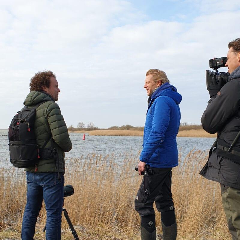 Opnames bij de Afsluitdijk door het programma: Vroege Vogels. Drie mannen staan op de foto. De ene heeft een camera en de anderen zijn in gesprek. Op de achtergrond zie je een plas en water.