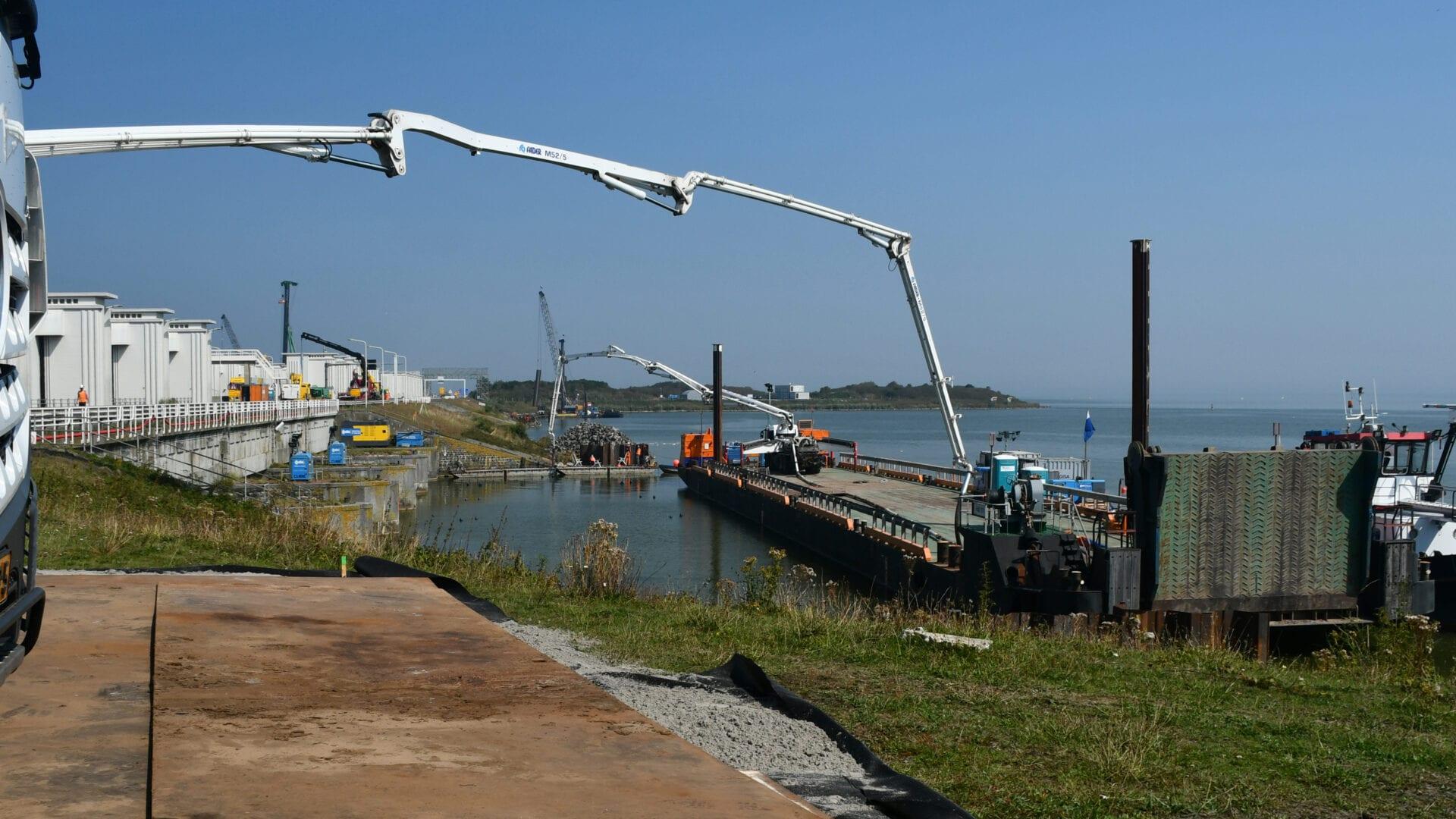 Wij zien een boot die het onderwaterbeton stort. De boot ligt in het water en links zie je een weg met witte sluisgebouwen bij Den Oever.