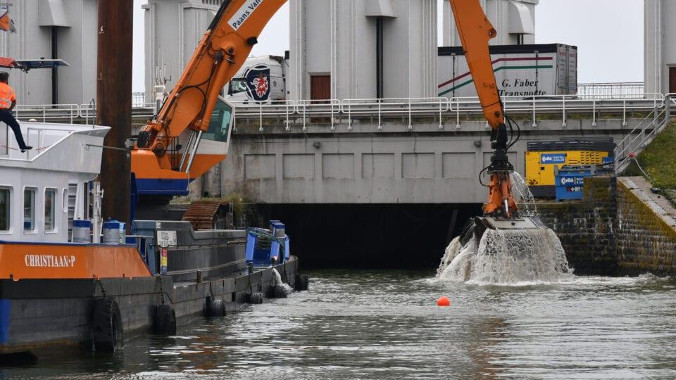 Wij zien een oranje boot met een hijskraan. Deze voert baggerwerkzaamheden uit voor de witte sluisgebouwen. Zij kraan haalt bodem uit het water.