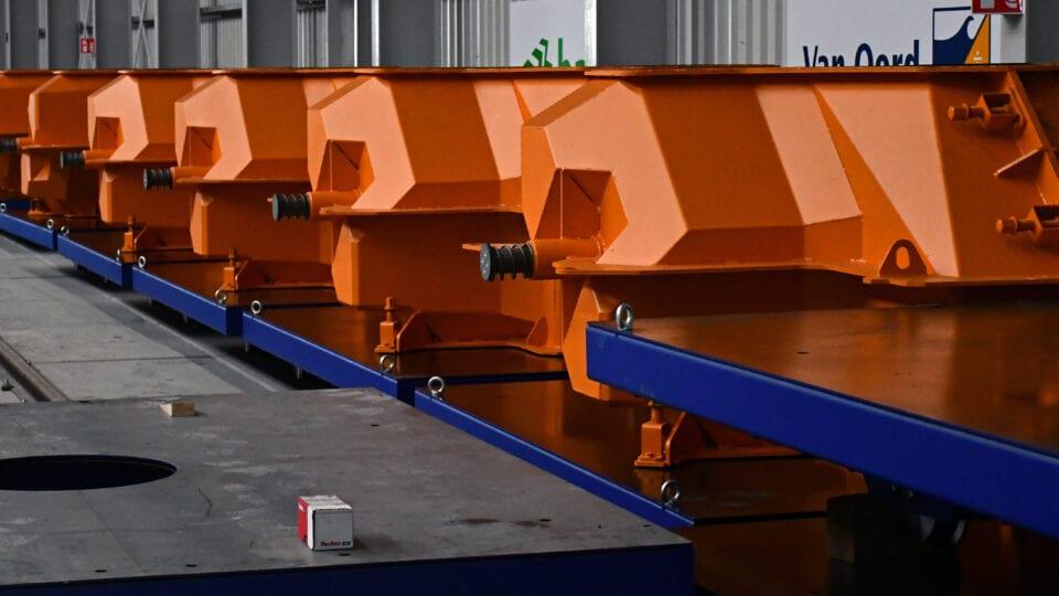 Foto van de mal voor productie van Levvel blocks. Wij zijn in een loods van Van Oord. Er staan allemaal oranje blokken in een rij.