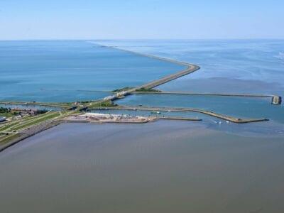 Luchtfoto van het Afsluitdijk Wadden Center, deze ligt links. De weg van de Afsluitdijk loopt van linksonder met een bocht naar linksboven. In het midden zien we de huizen van Kornwerderzand. Daarnaast het kantoor van DNA. Je ziet de weg die over de Afsluitdijk loopt. Aan de beide kanten van de weg zie je water.