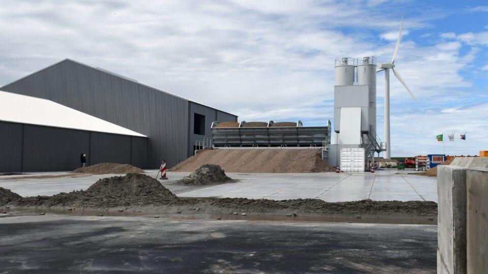 We zien een tekening van een industriegebied. Er zijn meerdere loodsen en achter een silo en windmolens. Hierin zitten grondstoffen.