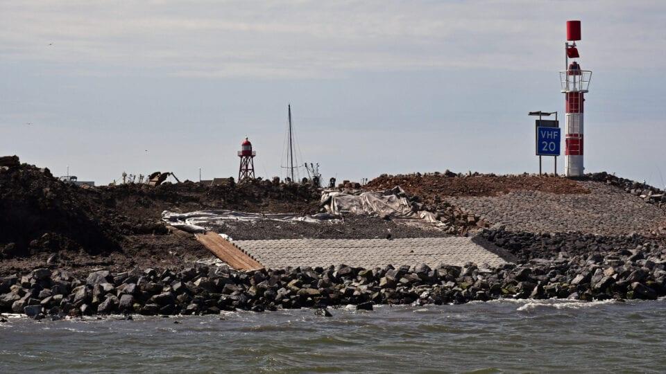 Wij zien een dijk aan het water. Achter het water zien we een verhoging met rotsen, stenen en cement. Bovenop de dijk staan twee vuurtorens of lichtbakens. Dit zijn rood, witte pilaren.