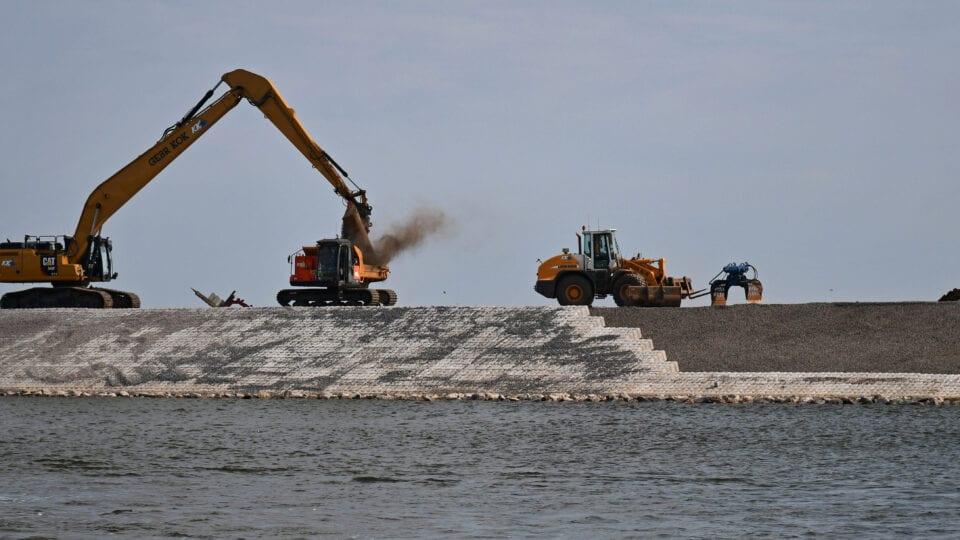 Vanaf het water kijken wij uit op de dijk. Er zijn drie kranen en tractoren bezig om werkzaamheden uit te voeren. Dit is om de dammen te renoveren.