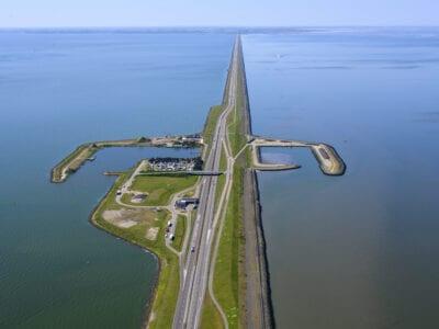 Luchtfoto van de Afsluitdijk bij Breezanddijk. Wij kijken van boven op de haven en camping bij Breezanddijk. Je ziet de weg van beneden naar boven lopen. Aan de zijkanten zie je water. De haven lijkt op een omgekeerde u, dit zijn landstroken waar boten kunnen aanmeren. Verder zie je een kleine camping en bouwterrein.